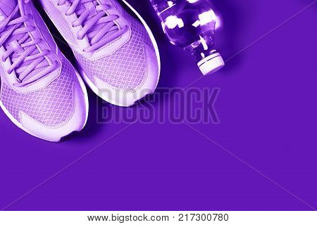 Ultra Violet sneakers and bottle of water on purple background. Concept of healthy lifestile, everyday training and force of will.