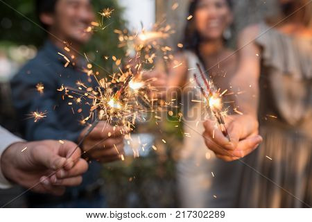 Burning sparklers in hands of party guests