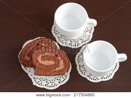 chocolate roll on napkins and empty cup
