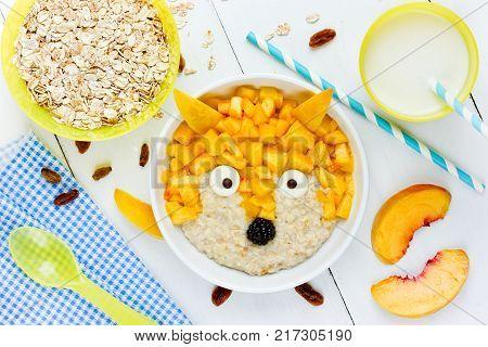 Baby healthy breakfast - sweet milk oatmeal porridge with peach shaped fox. Fun food idea for kids