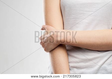Young girl with pain in the elbow. Isolated background.