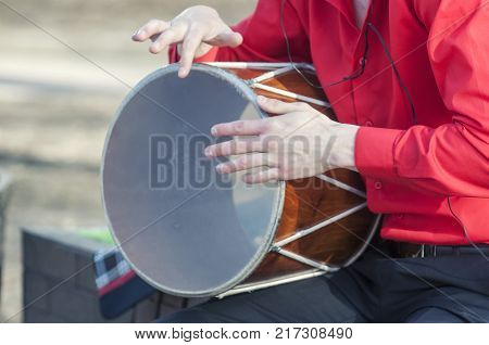 musician plays a traditional drum. Dhol can refer to any one of a number of similar types of double-headed drum widely used, with regional variations, throughout the Indian subcontinent.