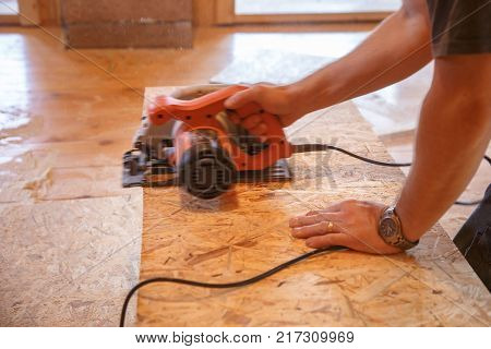 Worker using professional saw cutting the flakeboard (OSB). DIY professional work home improvement and renovation carpentry concept.