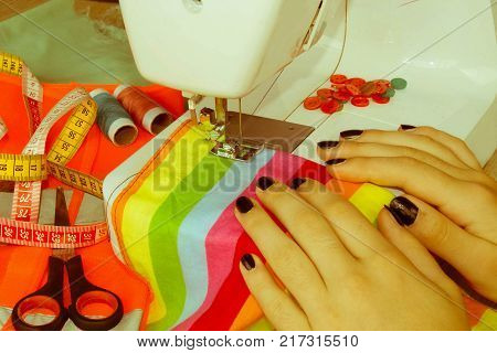 processes of sewing on the sewing machine sew women's hands sewing machine. Female tailor threading leather material on sewing machine