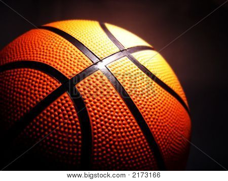 orange basketball against a dark background composed horizontally poster