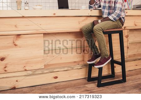 low section of african american man sitting at bar counter in cafe