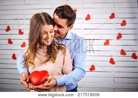Young couple on Valentine's Day. A loving couple hugs with a heart in their hands.