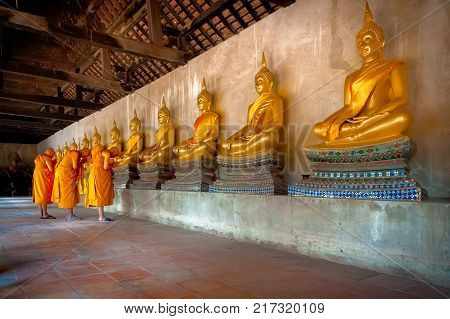 AYUTTHAYA, THAILAND - March 12, 2017: MONKS PRAY TO THE LORD BUDDHA.  Three monks bow and pray in front of the golden Buddha statues which are along cloister of Wat Phutthaisawan Temple