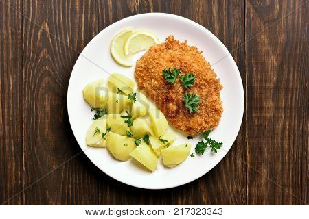 Schnitzel with boiled potato on plate over wooden background. Top view flat lay food