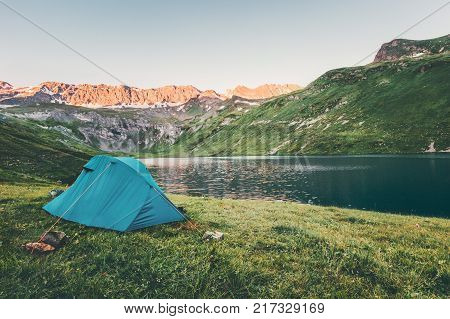 Tent camping at sunset Mountains and lake Landscape Travel Lifestyle concept Summer adventure recreation vacations outdoor