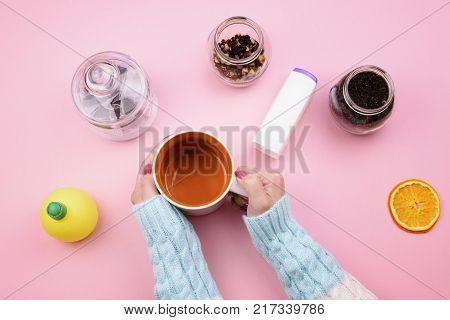 Cutlery, mug, tea, tea leaves, tea bags on a pink background, top view