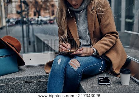 Moments of inspiration. Close up of young woman listening music using her smart phone and writing something down while spending carefree time in the city