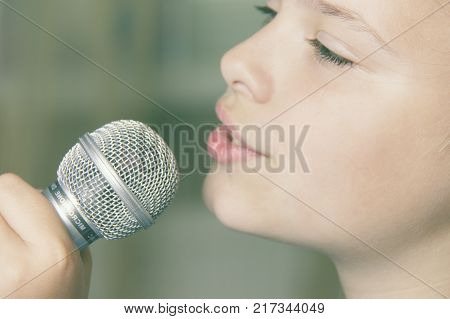 Closeup of singing caucasian child girl. Young girl emotionally sings into the microphone holding it with hand