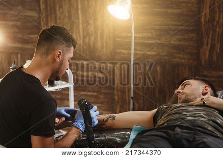 Professional Tattooer Artist Doing Picture On Hand Of Man By Machine Black Ink From A Jar. Tattoo Ar