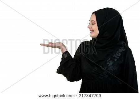 studio shot of young woman wearing traditional arabic clothing. she's holding her hand to the side.