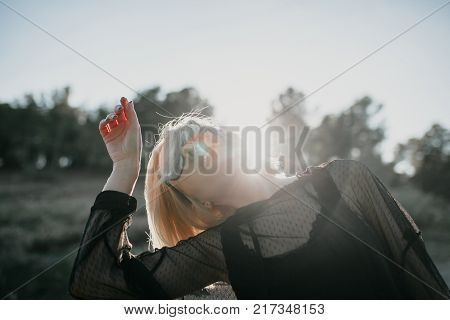 Rad blonde girl dancing and looking at the sky with sunglasses and black clothes.