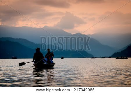 Silhouettes of people on boats at sunset on Phewa lake. Vanilla sky and mountain background.