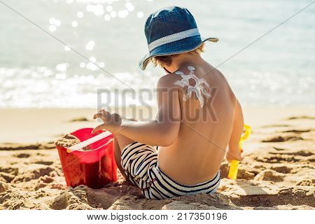 The Sun Drawing Sunscreen ,suntan Lotion On Baby Boy Back. Caucasian Child Is Sitting With Plastic C