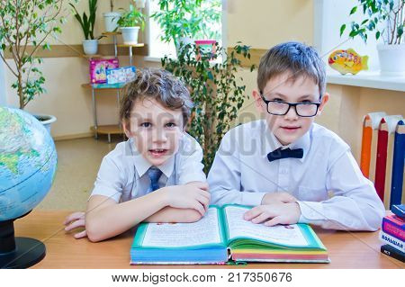 Russia Moscow first high school 2 class b - October 28 2017: Two small schoolboys sitting together at table in class reading the study book looking at camera