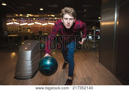 Condensed young man makes a bowling strike. The student is about to throw a ball for bowling