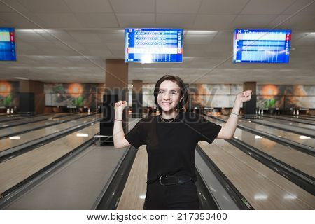 Happy girl made a bowling strike. Portrait of a cheerful girl playing bowling and joy lifting her arms up