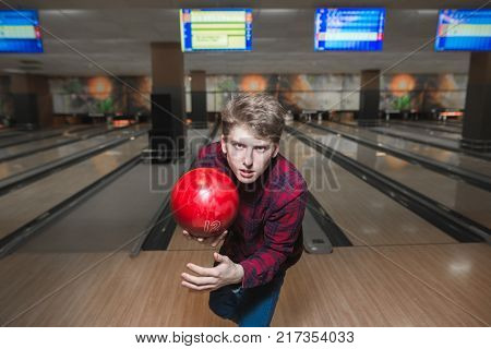 Portrait of a pissed young man with a bowling ball in his hands. A young man throws a bowling ball. Bowling game