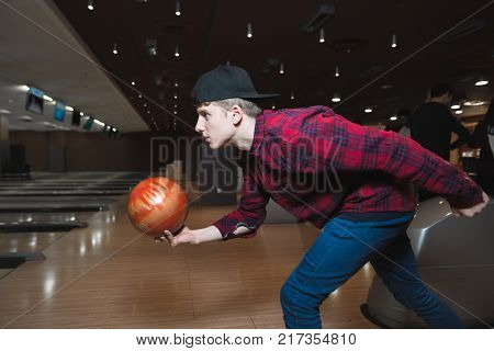 A student plays bowling. A young man makes a bowling balloon throw. Bowling on the track