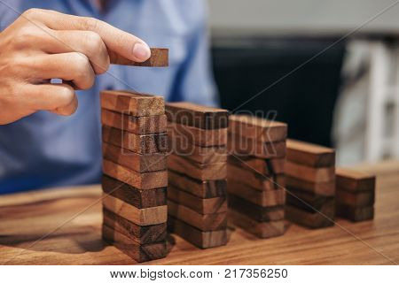 Alternative risk concept plan and strategy in business Risk To Make Business Growth Concept With Wooden Blocks hand of man has piling up and stacking a wooden block.