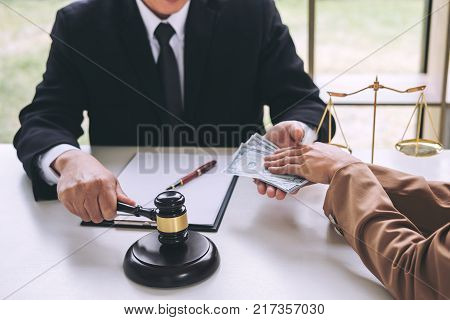 Bribery and corruption concept bribe in the form of dollar bills Businesswoman giving money to male lawyer while helps making deal to agreement a real estate contract and financial corporate.