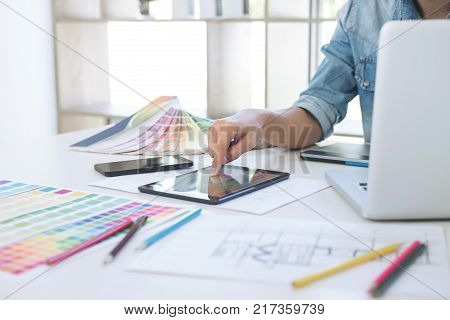 Color samples colour chart swatch sample Graphic designer being selecting Color table and graphics tablet pen at workplace with work example on wooden desk.