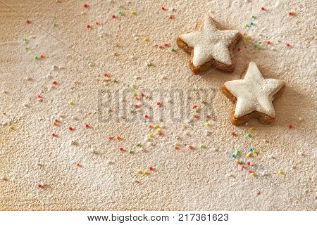 Christmas background with cinnamon stars sprinkles and sugar as snow