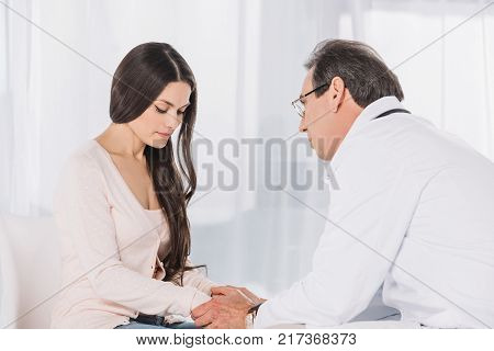 pregnant woman talking with doctor at clinic