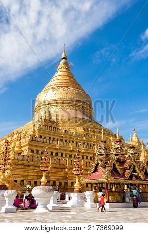 Bagan Myanmar - December 6 2014: Burmese people pray and worship at Shwezigon Paya one of Myanmar's most revered pagodas in Bagan Myanmar (Burma).