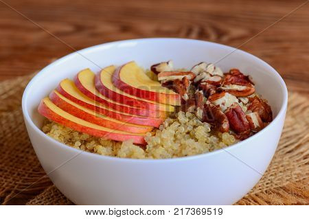 Quinoa porridge with fresh apples and nuts topping. Vegetarian quinoa porridge with apples and pecan nuts in a white bowl. Sweet dish. Rustic style. Closeup