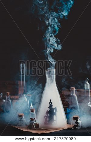 Lab bottle with haunted castle silhouette. Wizard workplace with smoke and magical equipment. Dark conceptual still life.