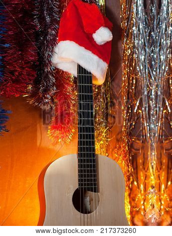 Classical guitar in the background of a Christmas background, red Santa hat, magical yellow light