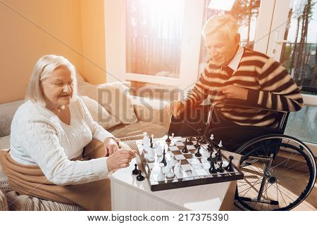 The senior man and woman play chess in the nursing home. A man is sitting in a wheelchair. The woman is covered with a blanket.