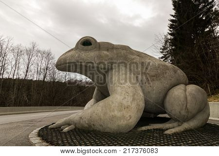 Austefjorden in Volda, Norway - April 19, 2017: Statue of a common toad, Bufo bufo, made by artist Robert Steinnes. A massive project have been going on to save the toads here from being hit by cars at the new road Kvivsvegen. This place is now a new tour