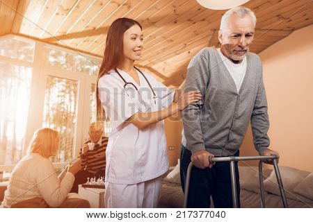 An asian nurse helps a man on an adult walker in a nursing home. It's hard for him to go himself. She supports a man.