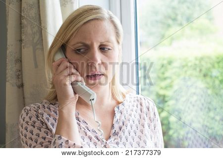 Close Up Of Worried Woman Answering Telephone At Home