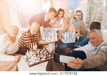 A group of young and old people in a nursing home make a selfie on a smartphone with an elderly woman. She has a birthday and she was given this mobile phone. She is very surprised and very happy.
