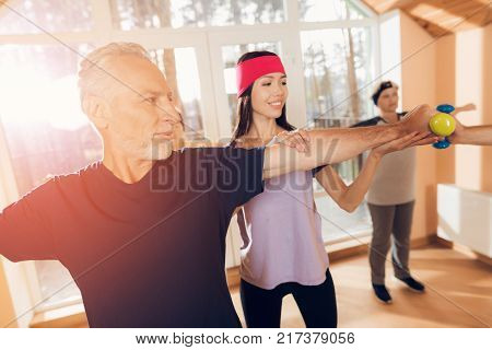 A group of elderly women and men doing therapeutic gymnastics. A young instructor is engaged with them. They are in a nursing home.