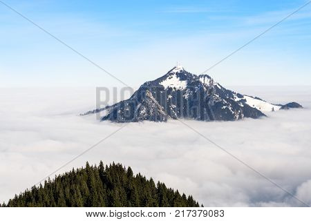 Mountain overtowers foggy cloud layer. Gruenten, Bavaria, Germany. Foresight and vision for business concept and ideas.