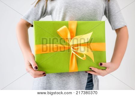 partial view of woman holding wrapped present in hands isolated on grey