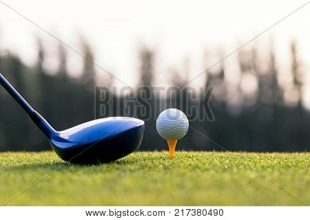 Close up golf ball and driver player doing golf swing tee off on the green sunset evening time presumably does exercise select focus. Healthy and Lifestyle Concept.
