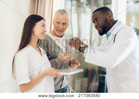 The doctor tells the nurse how an elderly male patient should take pills. The man hears it and he is very focused on the doctor's words. He is in a nursing home.