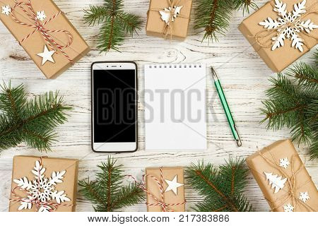Preparing for holidays background. Wishlist gift box mobile pen and garland frame top view on wooden table with copy space. Seasonal sales online sopping Christmas presents concept.