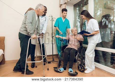 The doctor is talking to an elderly woman in a nursing home. He smiles. Nearby are medical staff and other senior men. A woman is sitting in a wheelchair. She is dripping a medical dropper.