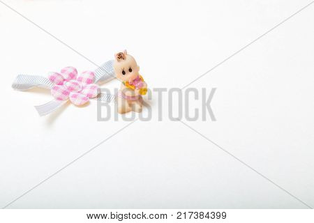 High angle view of cute little baby doll with brown curly hair wearing diaper with pacifier in mounth sitting on cloth flower with blue ribbon. close-up shot. with copy space. isolated on white background. high quality image