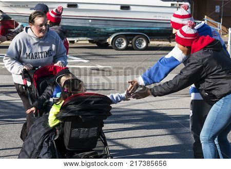 West Islip NY USA - 24 November 2017: Even the kids in a stroller get high fives as they get closer to the finish line of the annual Run Your Turkey Off 4K the day after Thanksgiving.